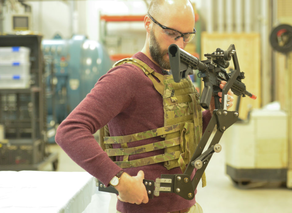 "Army Research Lab engineer Dan Baechle demonstrates how to strap on the ""Third Arm,"" a mechanical device designed to improve Soldiers' accuracy and reduce fatigue. (Photo Credit: U.S. Army photo by Joe Lacdan)"