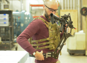 """Army Research Lab engineer Dan Baechle demonstrates how to strap on the """"Third Arm,"""" a mechanical device designed to improve Soldiers' accuracy and reduce fatigue. (Photo Credit: U.S. Army photo by Joe Lacdan)"""